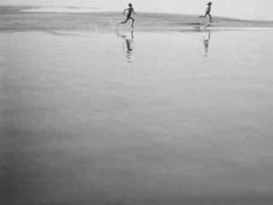 ЧЕТВЕРТЫЙ СОН ОБ ИВАНЕ, КОТОРЫЙ... ВИДИТ РЕКА... По воде и песку бежит девочка. Бежит Иван, стараясь догнать девочку. Иван обгоняет девочку и бежит, вытянув вперед руку.