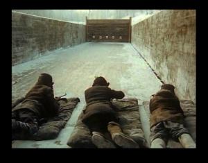 Военрук ведет с школьниками занятия на полигоне. Дети готовятся принять участие в войне: учатся стрелять с боевой позиции.