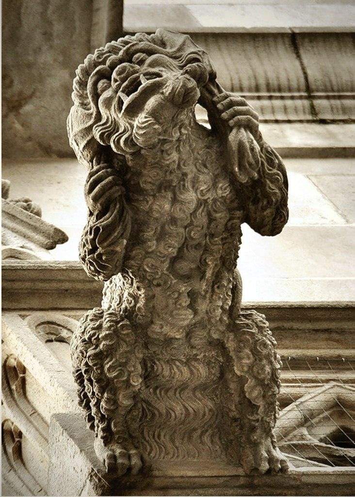 Барселонская горгулья неведомой породы. Не понять даже ее пол. Судя по прическе - женщина. По бороде - мужчина. Руки - человечьи. Ноги - зверьи. В шкуре что-то прячется. Кто это?