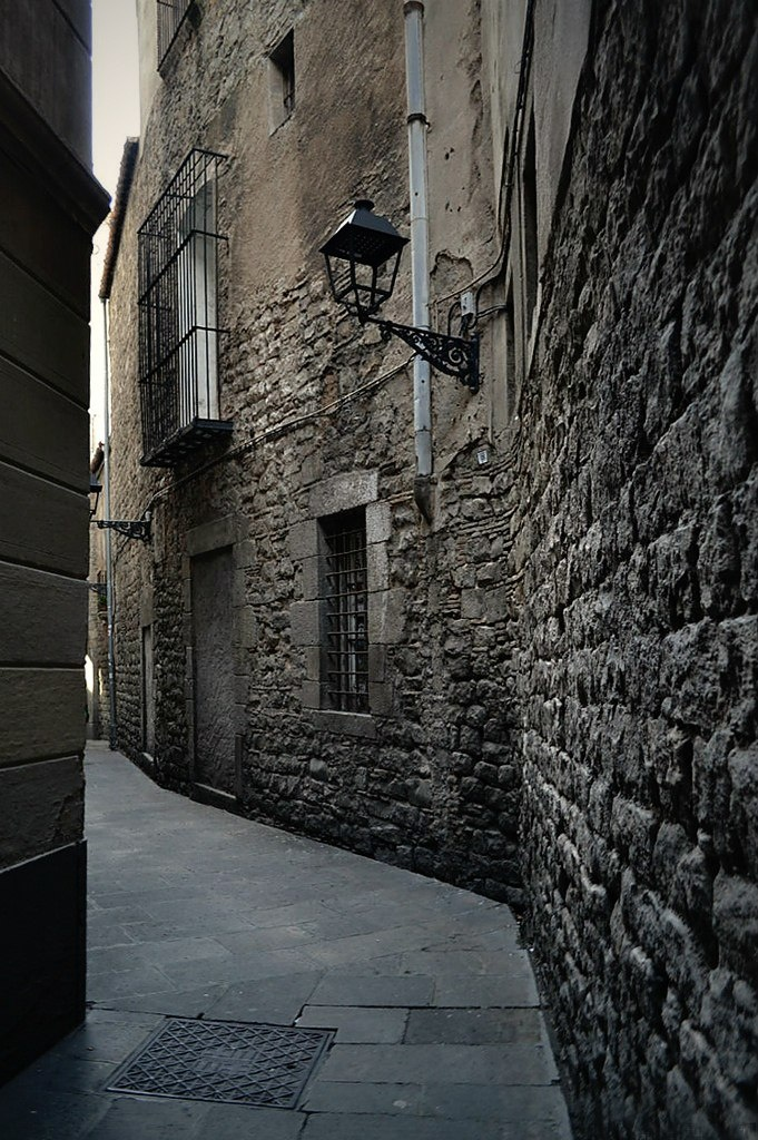 Барселона. Готический квартал. Одна из узких, кривых улочек квартала с домом, судя по массивной кладке, пришедшим из Римской эпохи.