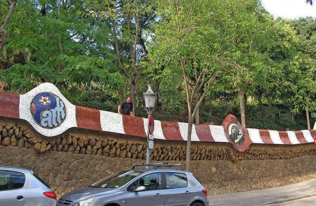 """Барселона, район Кан-Мунтанер-де-Далт, известный как Лысая гора (Монтанья Пелада, La montaña pelada). Улица Улот (Калье Olot). Ограда """"города-сада"""" с мозаичными надписями «Park Guell»."""