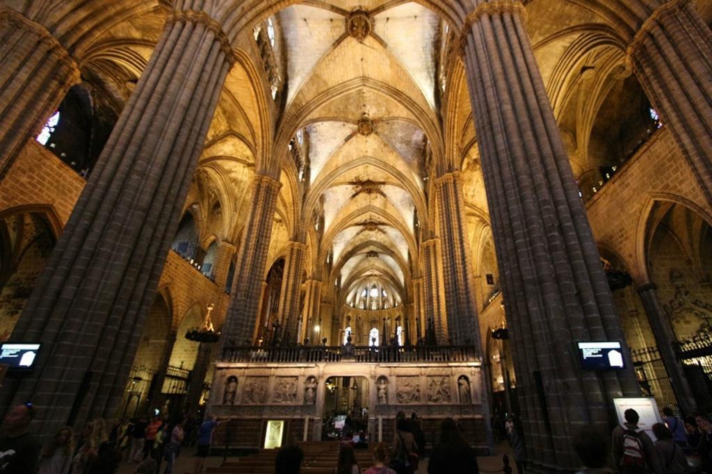 Кафедральный собор в Барселоне. Центральный вход в молитвенный зал, на главной оси которого стоит стена, обильно декорированная, зрительно прекращающая движение по глубинной оси к апсиде и Распятию...