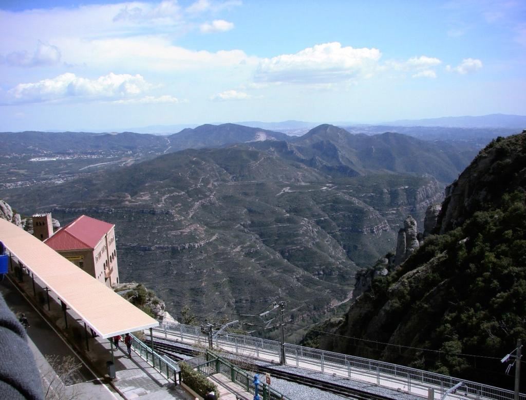 Вид с монастыря Монтсеррат на горный ландшафт, за которым прячется Барселона на берегу Средиземного моря.