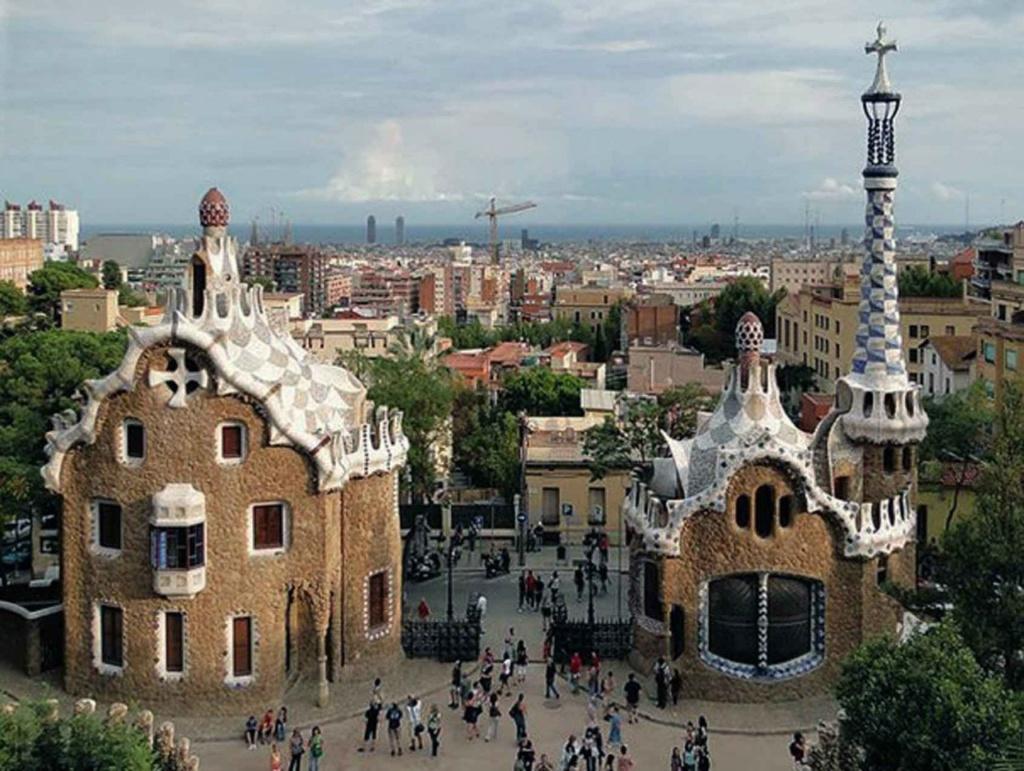 """Главный вход в Парк Гуэля с двумя павильонами. Павильон администрации - слева, Дом привратника - справа. За улицей Улот - застройка окраинной Барселоны домами """"без архитектуры"""". Вдали - Саграда Фамилия и Средиземное море."""