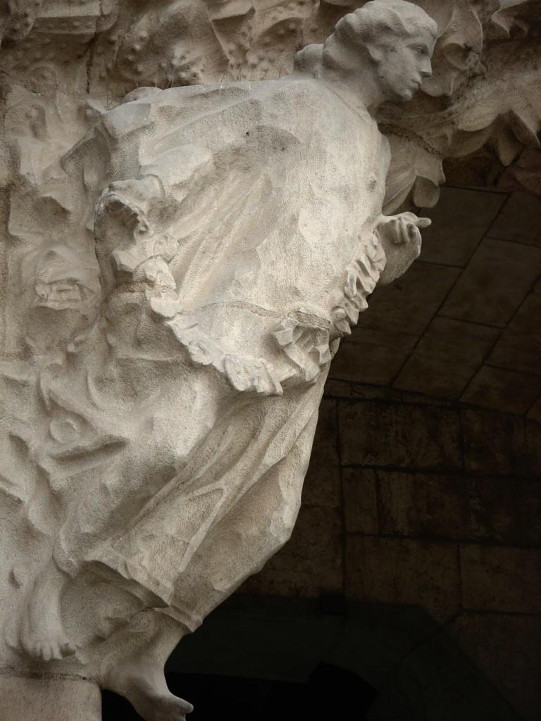 """САГРАДА ФАМИЛИЯ. Фасад """"РОЖДЕСТВА ХРИСТОВА"""". Центральный портал - """"МИЛОСЕРДИЕ"""". Нижний уровень: Ангел слева при входе в Храм."""