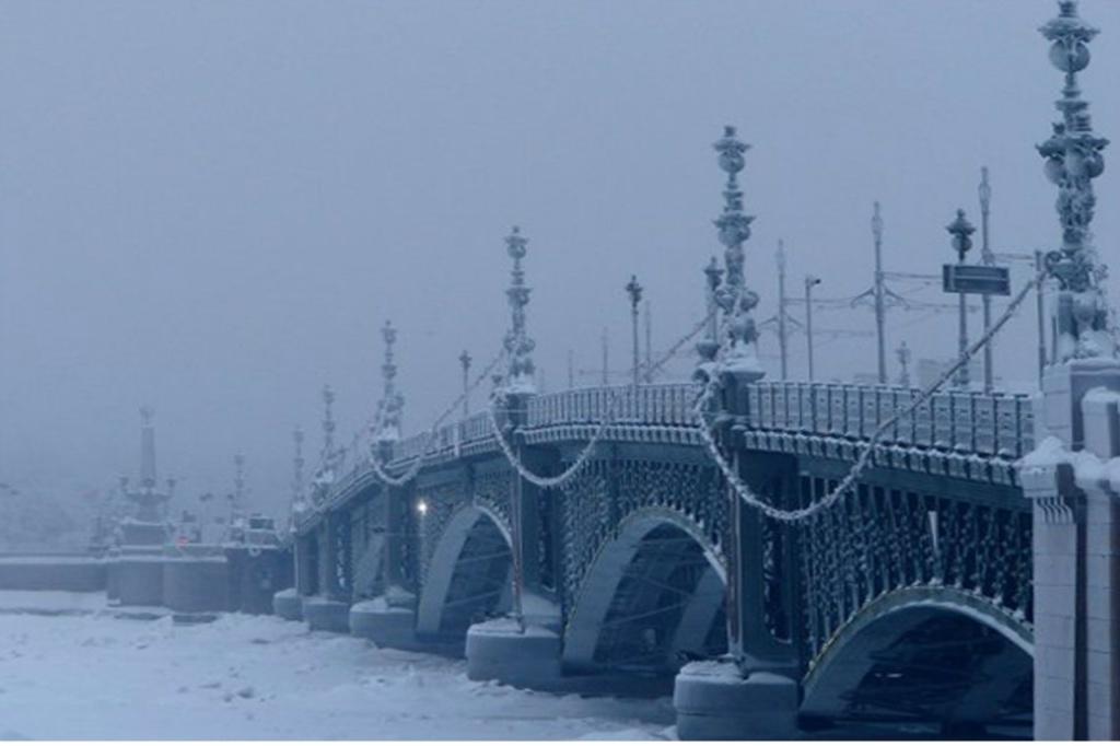 Вид Троицкого моста с той стороны, где Нева, движущаяся от Ладожского озера, под него втекает. Вдали - на Суворовской площади - можно разглядеть один из двух обелисков, двуглавым орлом увенчанных.