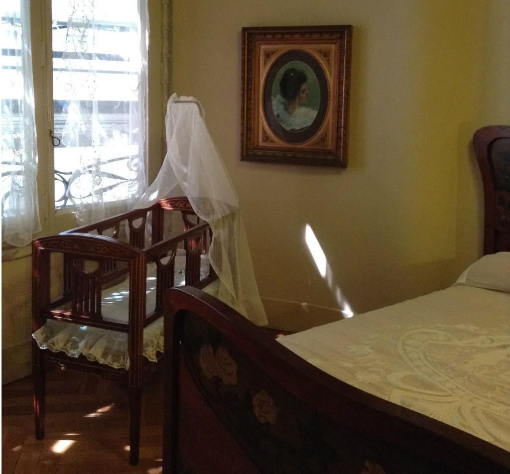 Каса Мила. Демонстрационная квартира, что оформлена в стиле 20-х годов XX века. Родительская спальня с детской кроваткой.