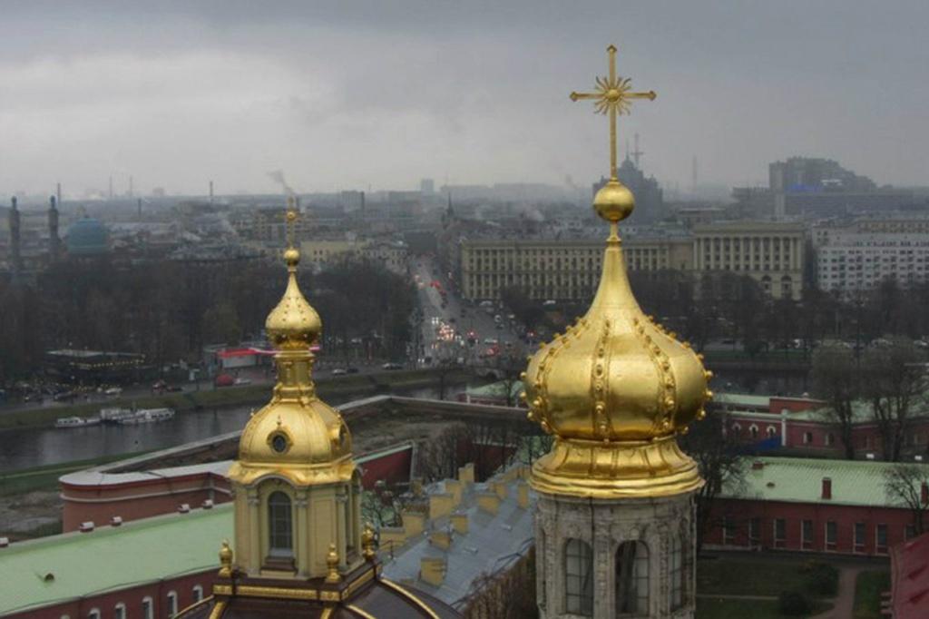 """Находящийся на высоте """"наш человек"""" имеет при себе фотоаппарат и тоже ведет наблюдение, только за Городом. Есть ближние объекты - сам Петропавловский собор с позолоченным завершием, Княжеская усыпальница рядом с ним."""