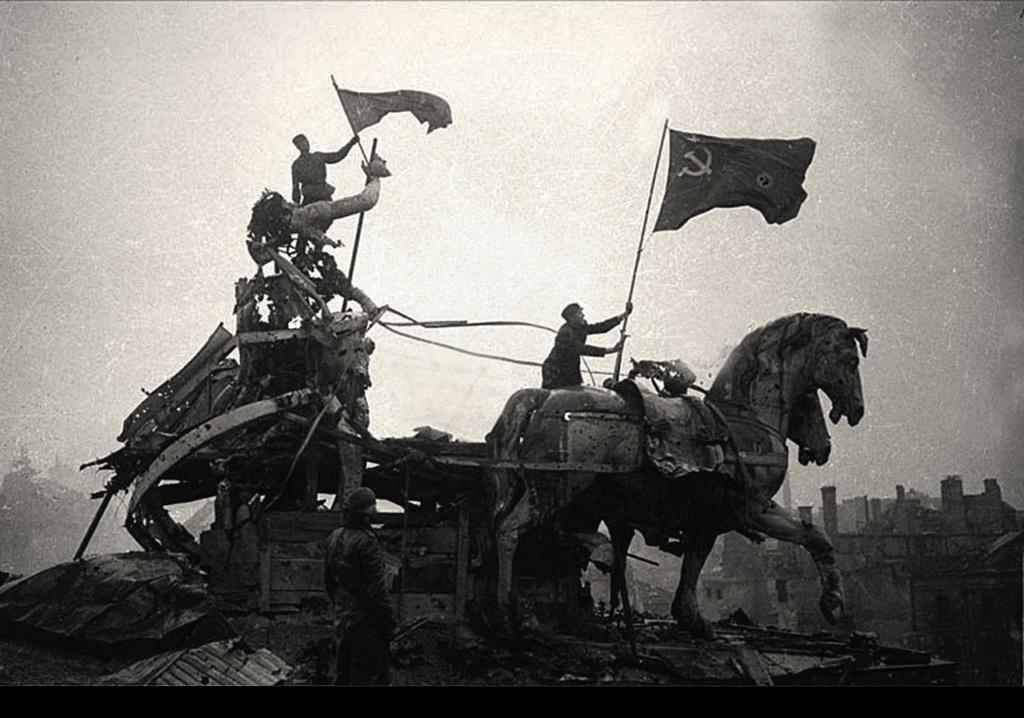 Советские воины устанавливают флаги на колеснице Славы над Бранденбургскими воротами...