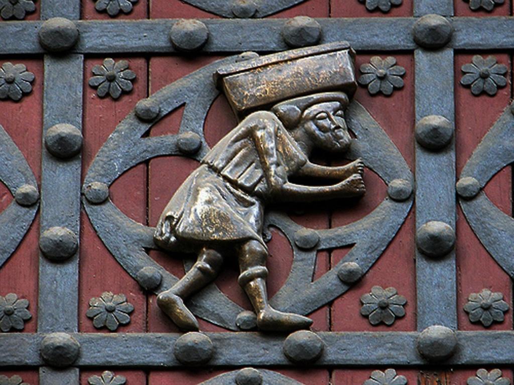 Церковь Санта-Мария-дель-Мар. Входные врата в церковь, в декор которых включены две бронзовые фигурки мужчин, несущих по огромному камню. Кто они такие?
