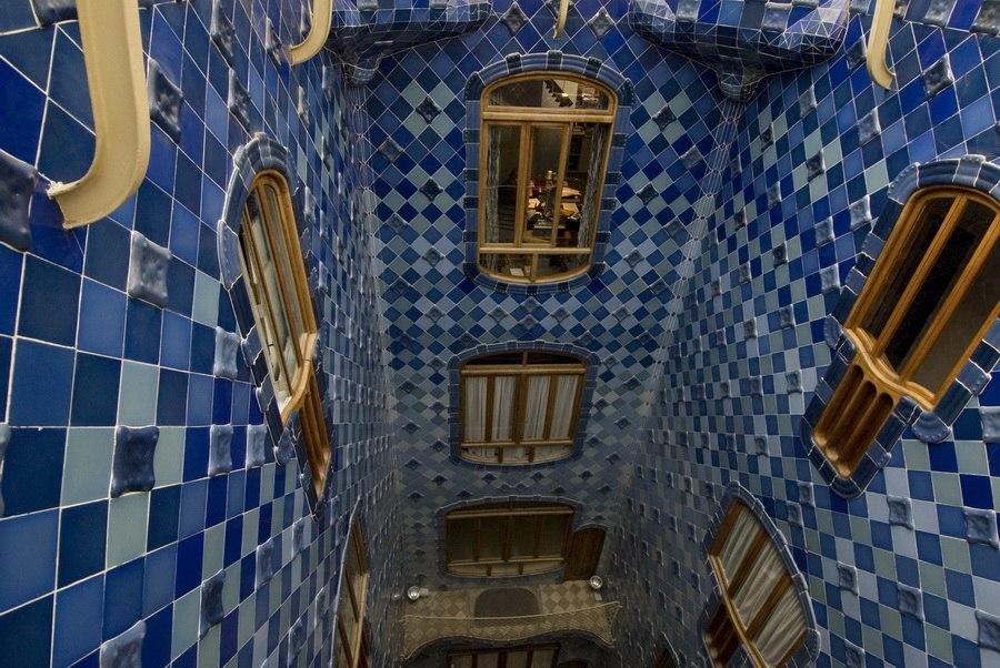 Барселона. Каса Бальо. Антонио Гауди. 1906. Внутренний двор со стенами, облицованными керамическими плитками, цвет которых меняется по высоте двора от синего до серого. Окна смотрят во двор, комнаты видят друг друга.