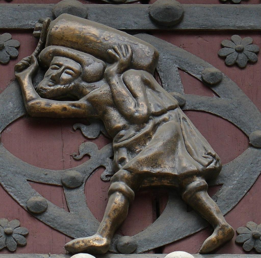 Церковь Санта-Мария-дель-Мар. Входные врата в церковь, в декор которых включены две бронзовые фигурки мужчин, несущих по огромному камню или мешку со строительными материалами. Кто они такие?