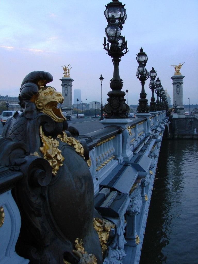 По сторонам от въезда на мост возвышаются 17-метровые столбы, над которыми парят бронзовые фигуры, символизирующие Сельское хозяйство, Искусство, Войну и Сражение.