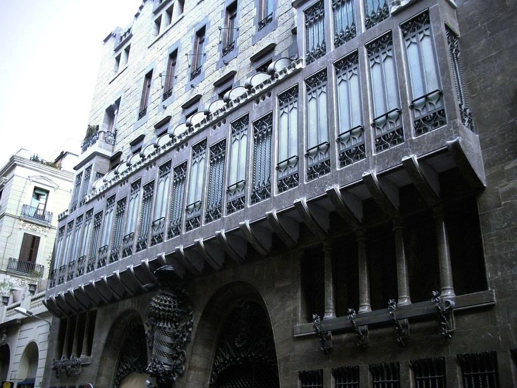Барселона. Улица Каррер-Ноу-де-ла-Рамбла. Дворец Эусебио Гуэля, построенный в 1885-1890 архитектором Антонио Гауди, а в 1985 году внесенный в список Всемирного наследия ЮНЕСКО. Главный фасад Дворца с эркером (трибуной) на консолях.