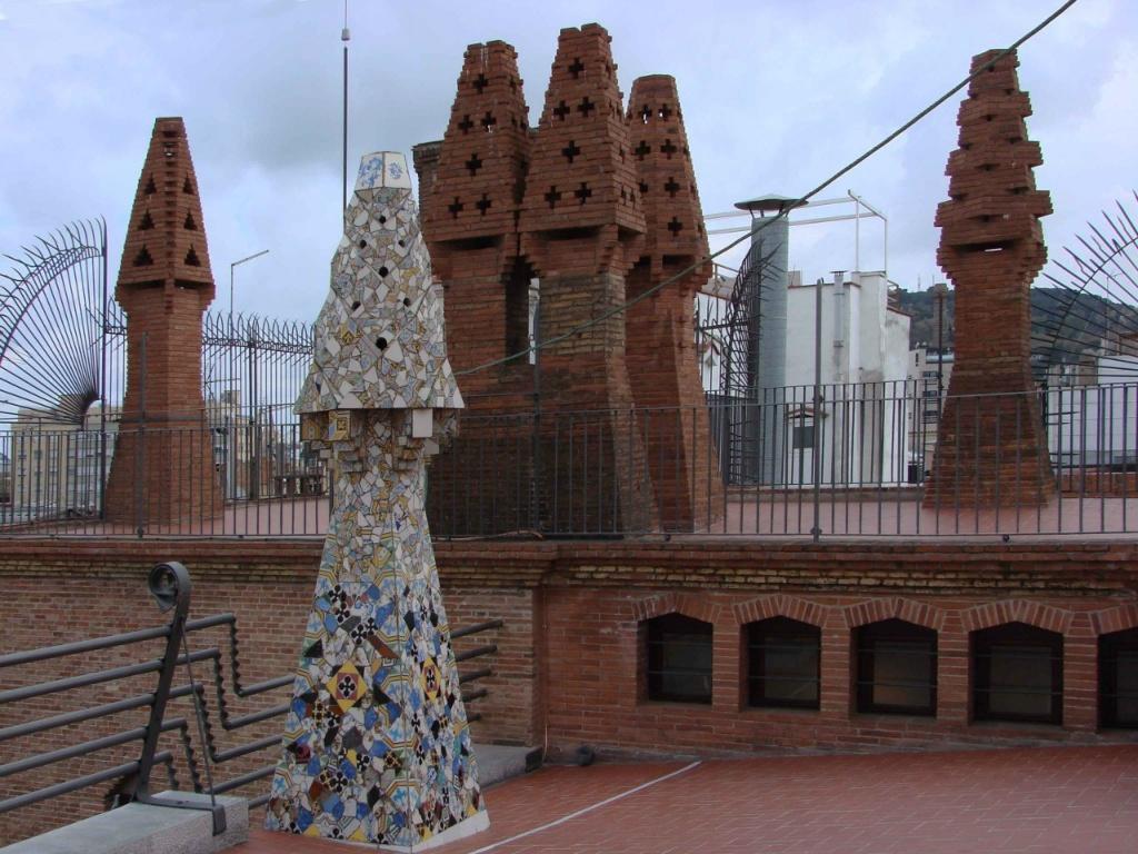 Башенка на переднем плане облицована колотой керамической плиткой. Здесь Гауди впервые использовал технику ТРЕНКАДИС, ставшую характерной чертой каталонского модерна. В дальнейшем использование этой техники стало для Гауди типичным.