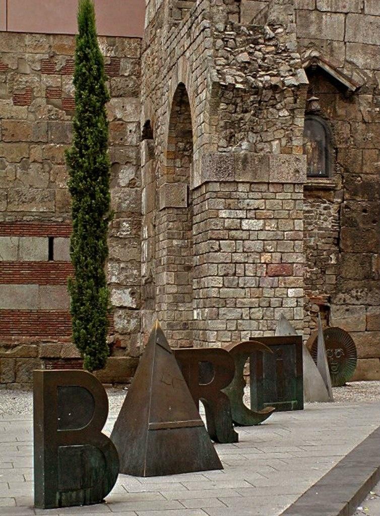 Реконструкция римского акведука. Перед ним - скульптурная группа работы Жуана Броссы, выполненная из семи букв, которые составляют римское название города – Barcino: БАРСИНО. 90-е годы XX столетия..