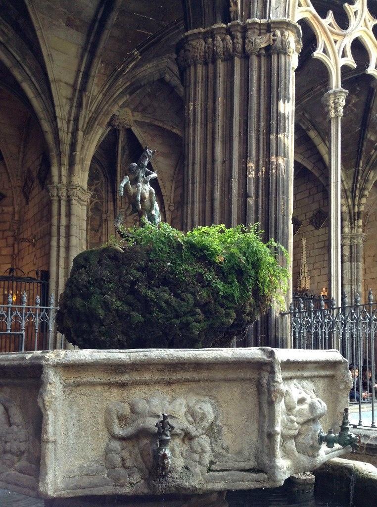 Клуатр в Кафедральном соборе Барселоны . Статуя Георгия Победоносца и фонтан с освященной водой.