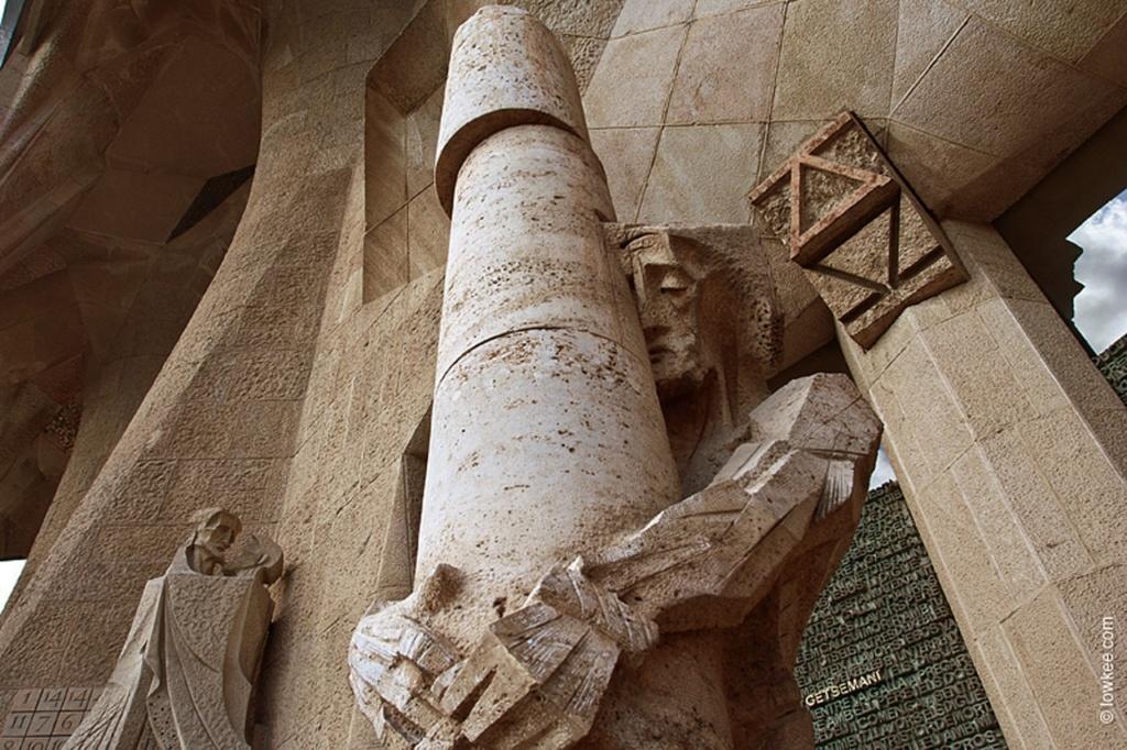 """Позади колонны означены Альфа и Омега, символизирующие Иисуса – начало и конец.ФАСАД СТРАСТЕЙ ХРИСТОВЫХ. Центральный портал: """"БИЧЕВАНИЕ ХРИСТА""""."""