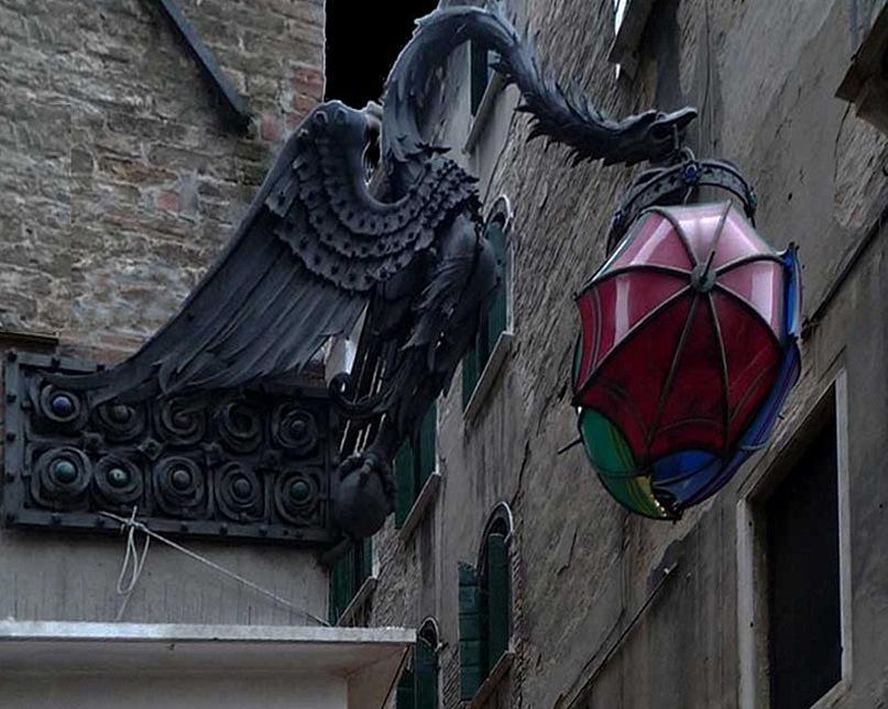 Венецианский декор настенный - Василиск держит в клюве фонарь, на игрушку из зонтиков похожий. Василиск - увенчанная короной химера с ядовитым дыханием, клювом и когтями, способная убивать взглядом. Что ему-то здесь делать? То, что Кем-то задано.