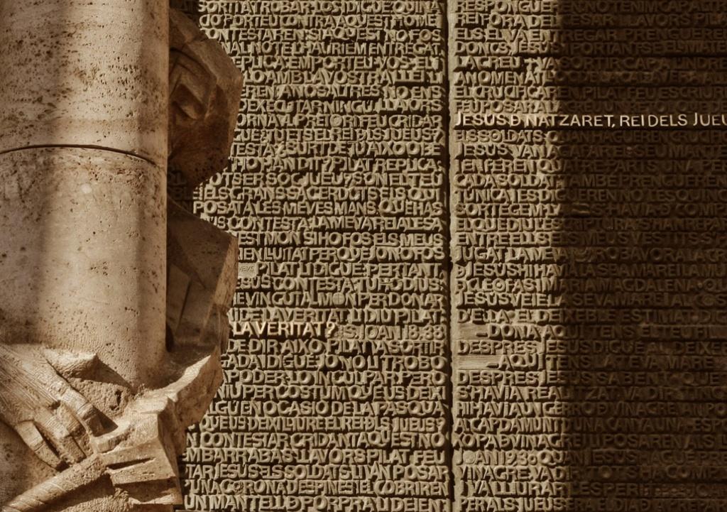 """""""ФАСАД СТРАСТЕЙ ХРИСТОВЫХ"""". Центральный портал: """"БИЧЕВАНИЕ ХРИСТА"""". На двери воспроизведен текст из Библии о последних днях Христа на разных языках, включая Каталонский. Всего 8000 букв. Золотом выделен вопрос «В чем истина?»"""