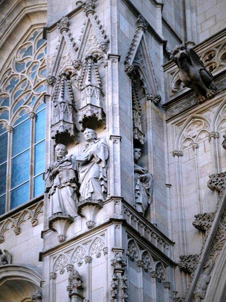 Фрагмент главного портала Кафедрального собора в Барселоне (XIX - XX век) с фигурой горгульи, что выбирается из каменных кружев, насмешливо глядя на туристов, стекающихся на соборную площадь. Она знает о людях что-то свое, но не проговаривается...