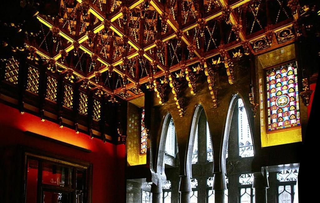 Барселона. Дворец Гуэля. Архитектор Гауди. 1885—1890 годы Бельэтаж. Приемный зал для высокопоставленных лиц. Арочно-колонная стена-завеса и золотой деревянный потолок. Слева - портал, ведущий в дамскую туалетную комнату.