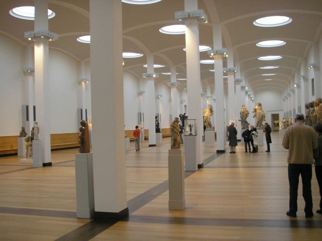 В центре здания находится главное фойе с двумя рядами колонн, плоским сводом и 32 стеклянными куполами. Архитектура Галереи прекрасна, потому что, можно сказать, ее нет - есть только то, что впускает в залы свет и заставляет перемещаться в пространстве.