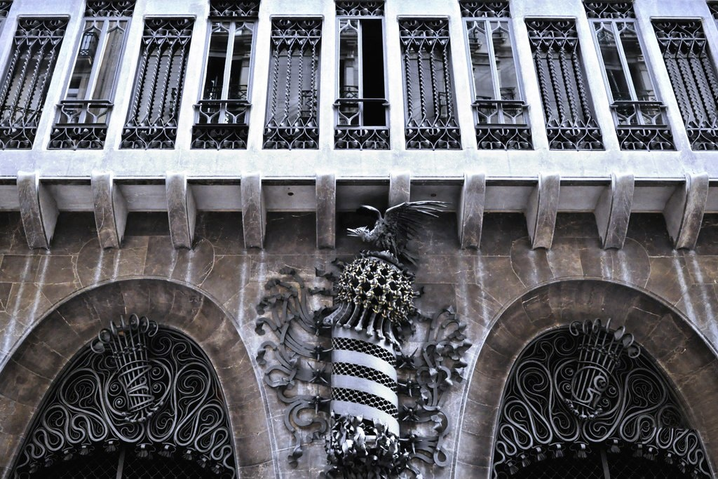 Дворец Гуэля. Главный фасад, выходящий на узкую улицу Nou de la Rambla. Композиция из кованого железа - двухметровый «фонарь», изображающий полосатый герб Каталонии, увенчанный своеобразным шлемом с крылатым орлом. Ажурная решетка ниже.