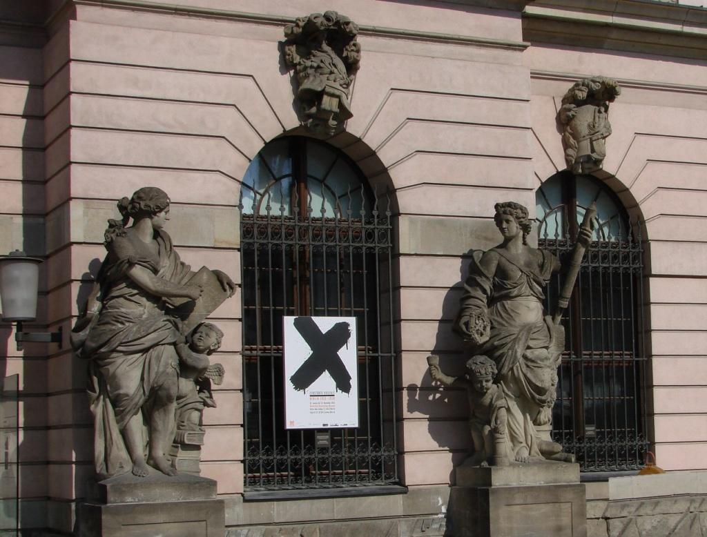 Арх. Андреас Шлютер. Здание Берлинского арсенала. Главный фасад. Четыре женские фигуры символизируют пиротехнику, арифметику, геометрию и механику. Это объявление сообщает, что открыта внутри выставка, посвященная фашистскому режиму...