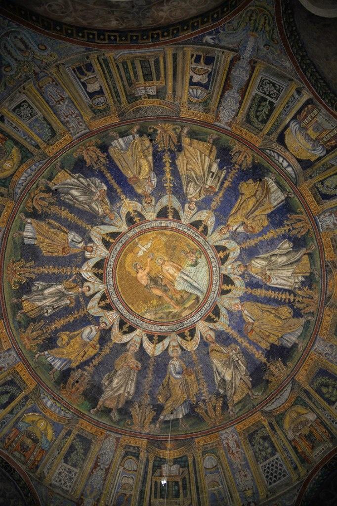 Базилика Сант Аполлинаре Нуово. Вокруг медальона, изображающего крещение Христа, помещены фигуры двенадцати апостолов, на которых нисходит благодатная энергия, изображённая радиальными лучами.