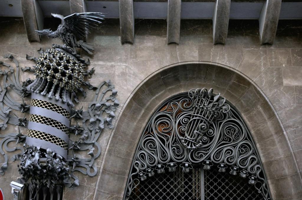 Дворец Гуэля. Главный фасад, выходящий на узкую улицу Nou de la Rambla. Монументальный въезд с великолепным порталом в виде высокой параболической арки, по форме повторяющей перевернутую провисшую цепь, закрепленную с двух концов.
