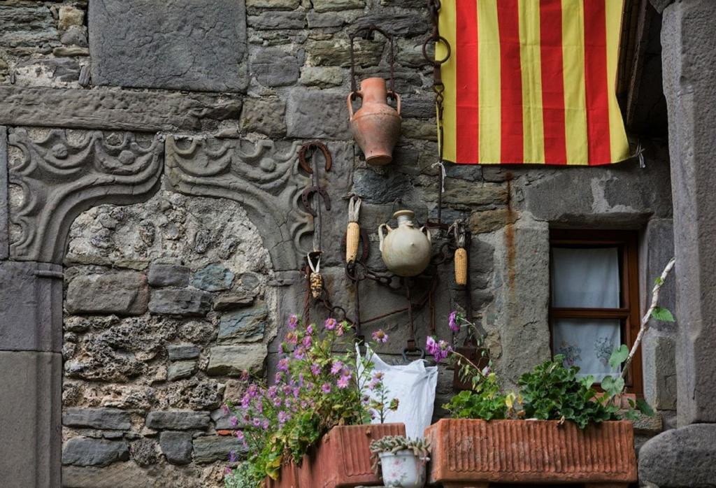"""Дом, старающийся удержать выдуманное счастье. На стене - подковы, какие-то коренья... Может быть, то """"ведьмины мешочки""""? Сосуды с """"наварами"""". Каталонский флаг - крик независимости. А резной портал заложен камнем, окно занавешено.."""