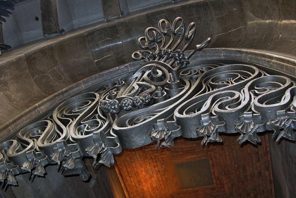 Дворец Гуэля. Главный фасад.. Один из двух монументальных въездов с великолепными порталами. Орнамент из кованого металла в верхней части высокой параболической арки.