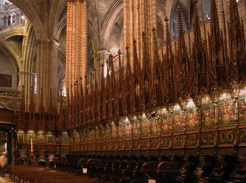 Кафедральный собор в Барселоне. Деревянные кресла, украшенные разноцветными позолоченными гербами рыцарей Ордена Золотого руна. Венчающие их пинакли завершены в конце XV в. немецким мастером Лохнером.