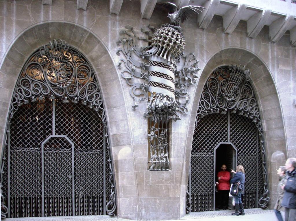 """Дворец Гуэля. Главный фасад, выходящий на узкую улицу Nou de la Rambla. Первый этаж здания с въездными воротами и декоративным """"фонарем"""" - гербом Каталонии...."""