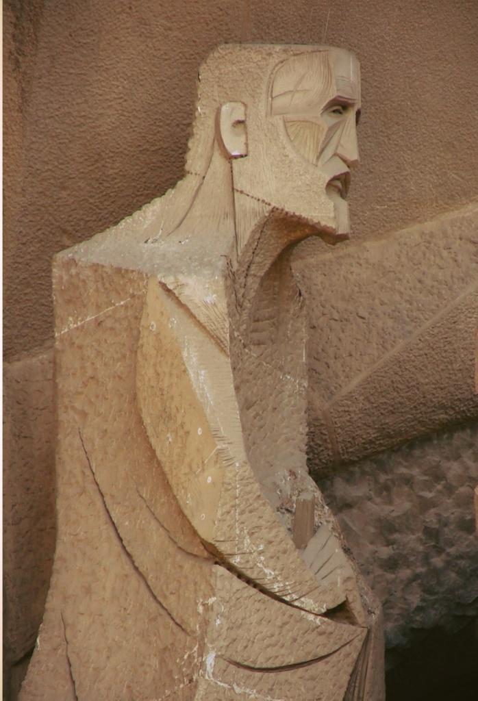"""Фасад """"СТРАСТЕЙ ХРИСТОВЫХ"""". Средний уровень главного портала: """"ВЕРОНИКА И ПЛАТ С ОТПЕЧАТКОМ ЛИЦА ИИСУСА"""". Крайняя фигура слева, так называемый, Евангелист в образе Гауди"""
