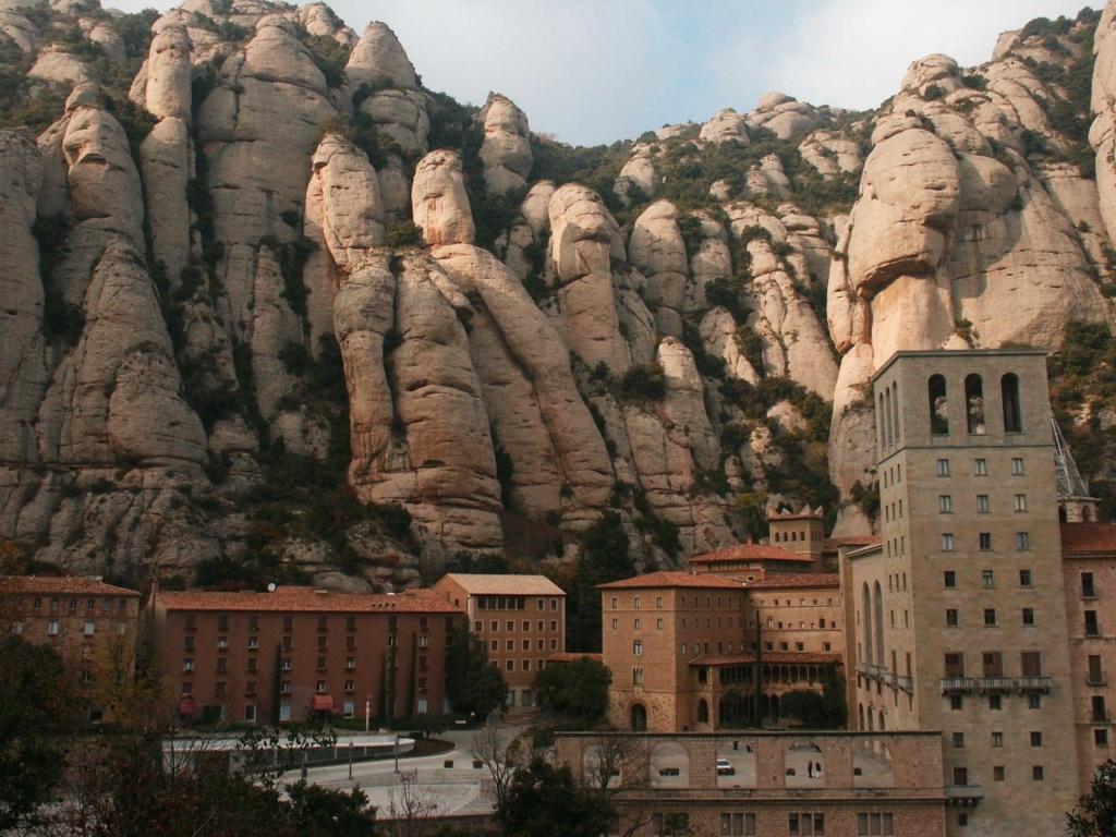 Вид монастыря над обрывом под грядой гигантов - скал...