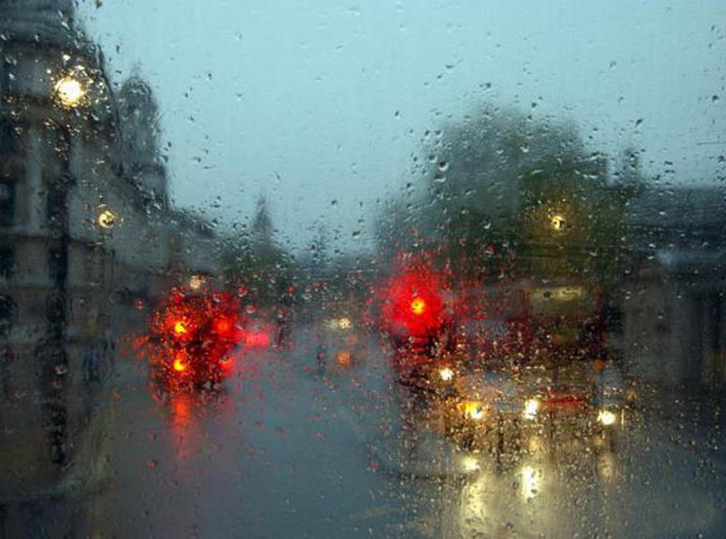 Вид из окна автобуса, размытый в дождевых каплях...